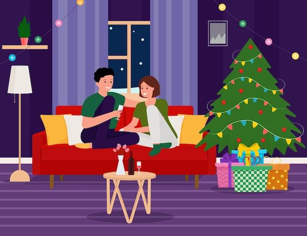 Szczęśliwa kobieta i mężczyzna siedzący obok choinki trzymający kubek wina boże narodzenie wnętrze