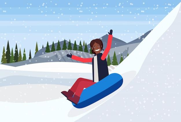 Szczęśliwa kobieta na sankach na śnieżnej gumowej tubce w górze