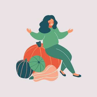 Szczęśliwa kobieta siedzi na stosie dyni z otwartymi ramionami. sezonowa kompozycja zbiorów z naturalnym zdrowym jedzeniem
