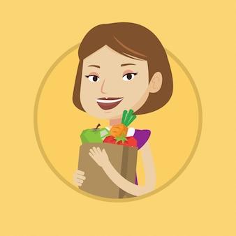 Szczęśliwa kobieta trzyma sklep spożywczy torba na zakupy.