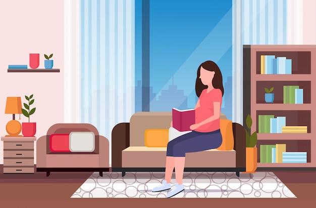 Szczęśliwa kobieta w ciąży siedzi na kanapie czytanie książki dziewczyna trzyma jej guz dziewczyna ciąża koncepcja matherhood nowoczesny salon wnętrze pełnej długości poziomej