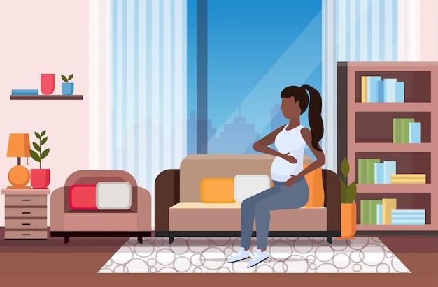 Szczęśliwa kobieta w ciąży siedzi na kanapie dziewczynka trzyma jej guz dziewczyna ciąża koncepcja matherhood nowoczesny salon wnętrze pełnej długości poziomej