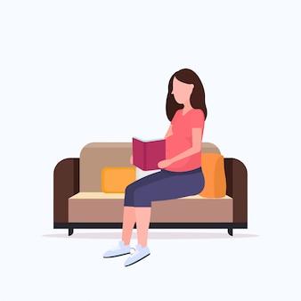 Szczęśliwa kobieta w ciąży siedzi na kanapie i czytając książkę dziewczyna trzyma jej guz dziewczyna ciąża koncepcja matherhood pełnej długości