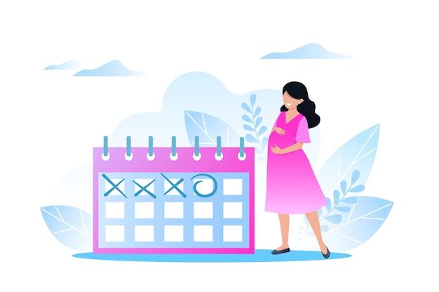 Szczęśliwa kobieta w ciąży stoi w pobliżu kalendarza, czekając na dzień porodu, przyszła mama