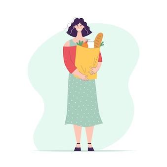 Szczęśliwa kobieta z papierową torbą pełną artykułów spożywczych