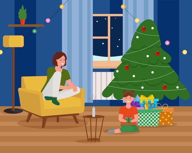 Szczęśliwa matka i jej córka siedzi obok choinki. przytulne świąteczne wnętrze. prezenty pod drzewem.
