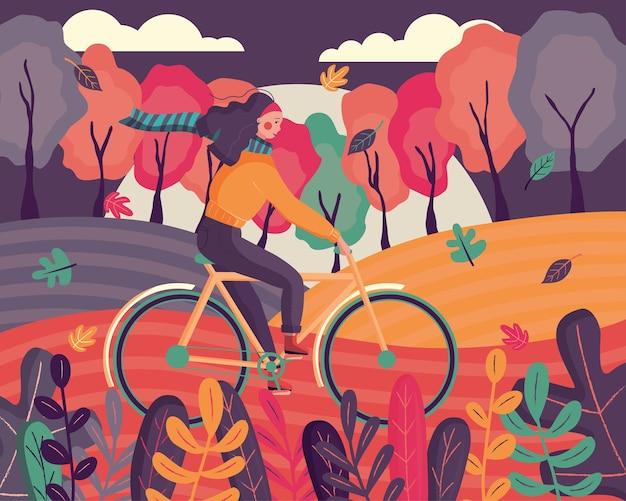 Szczęśliwa młoda kobieta ubrana w jesienne ubrania, jazda na rowerze w lesie