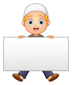 Szczęśliwa muzułmańska chłopiec kreskówka trzyma puste miejsce znaka
