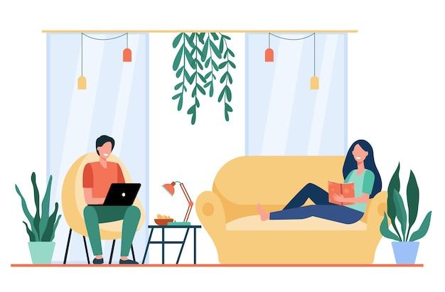 Szczęśliwa para odpoczywa na kanapie i w fotelu w salonie, czytając książkę, oglądając film na laptopie.