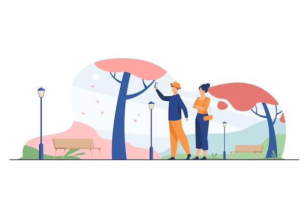 Szczęśliwa para przy selfie w parku jesień. spadek, miłość, sezon płaski wektor ilustracja. data i weekend