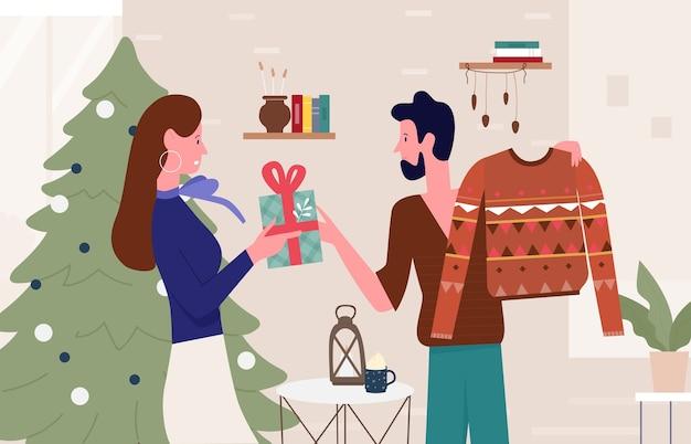 Szczęśliwa rodzina lub para osób daje prezenty świąteczne w domu