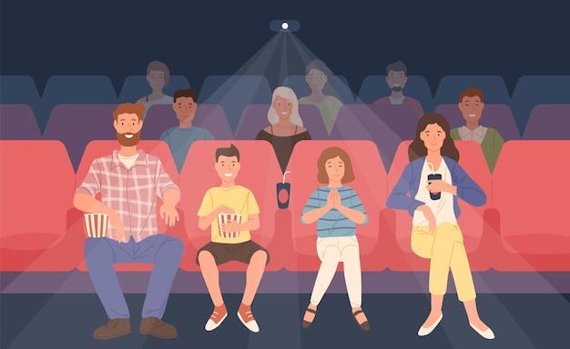 Szczęśliwa rodzina siedzi w kinie lub sali kinowej