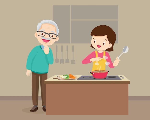 Szczęśliwa rodzina z dziadkiem i matką gotuje w kuchni, starsza kobieta gotuje