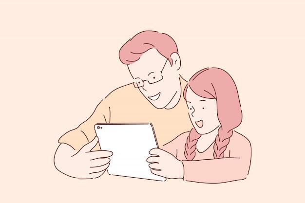 Szczęśliwa rodzinna rozrywka. ojciec i córka oglądają wideo na tablecie, brat i siostra grają w gry online, wesołe rodzeństwo, nastolatkowie lubią gadżety. proste mieszkanie