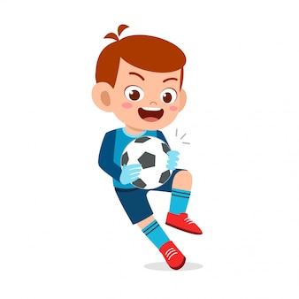 Szczęśliwa śliczna dzieciak chłopiec bawić się futbol