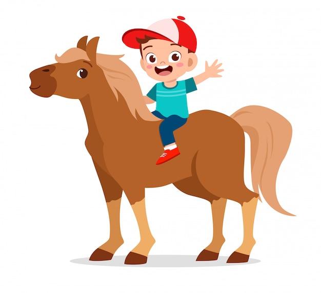 Szczęśliwa śliczna dzieciak chłopiec jedzie konia