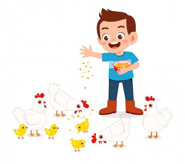 Szczęśliwa śliczna dzieciak chłopiec karmi ślicznego kurczaka
