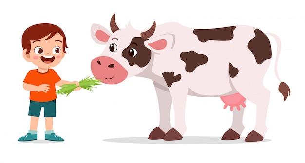 Szczęśliwa śliczna dzieciak chłopiec karmi ślicznej krowy