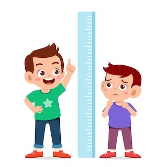 Szczęśliwa śliczna dzieciak chłopiec mierzy wysokość wpólnie