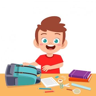 Szczęśliwa śliczna dzieciak chłopiec przygotowywa torbę dla szkoły