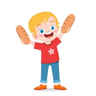 Szczęśliwa śliczna dzieciak chłopiec trzyma świeżego chleb