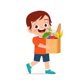 Szczęśliwa śliczna dzieciak chłopiec trzyma świeżych sklepy spożywczych