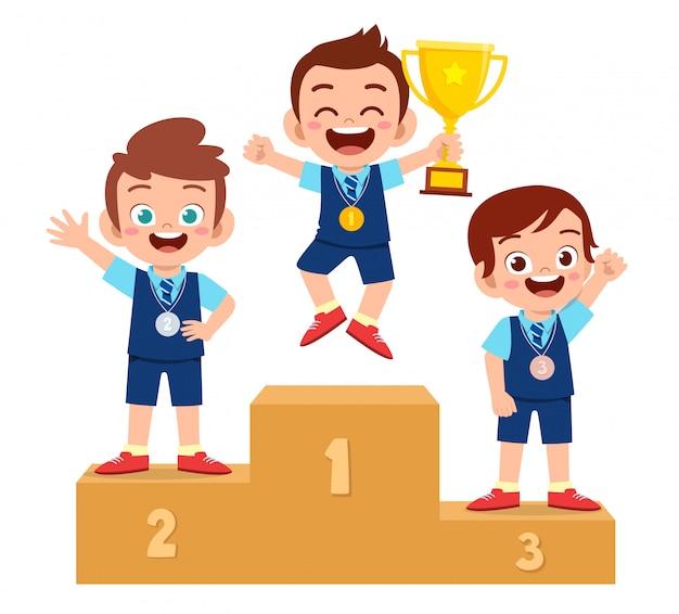 Szczęśliwa śliczna dzieciak chłopiec wygrywa na podium