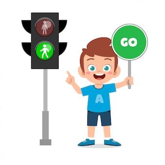 Szczęśliwa śliczna dzieciak chłopiec z ruchu drogowego znakiem