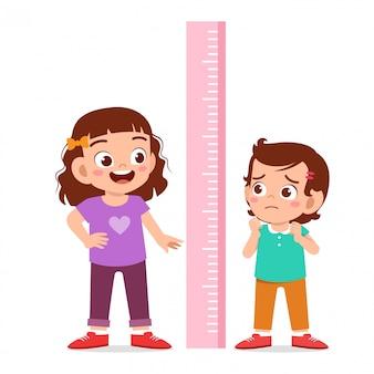 Szczęśliwa śliczna dzieciak dziewczyna mierzy wzrost wpólnie