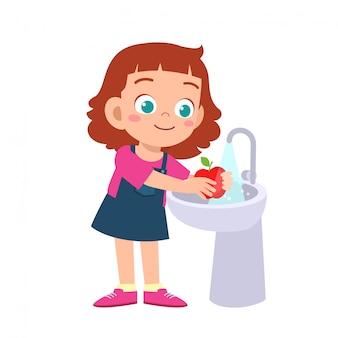 Szczęśliwa śliczna dzieciak dziewczyna myje jarzynowego owoc czysty