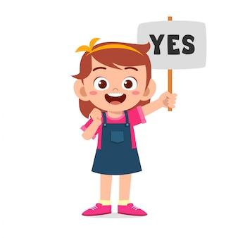 Szczęśliwa śliczna dzieciak dziewczyna niesie poprawnego znaka
