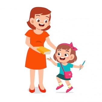 Szczęśliwa śliczna dzieciak dziewczyna przygotowywa iść do szkoły z mamą