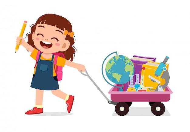 Szczęśliwa śliczna dzieciak dziewczyna przynosi książkę szkoła