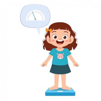 Szczęśliwa śliczna dzieciak dziewczyna używa skala wagi