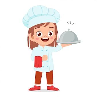 Szczęśliwa śliczna dzieciak dziewczyna w szefa kuchni kostiumu