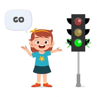Szczęśliwa śliczna dzieciak dziewczyna z ruchu drogowego znakiem