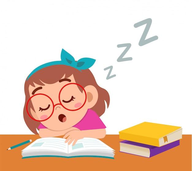 Szczęśliwa śliczna dziewczyna śpi podczas gdy studiuje w klasie