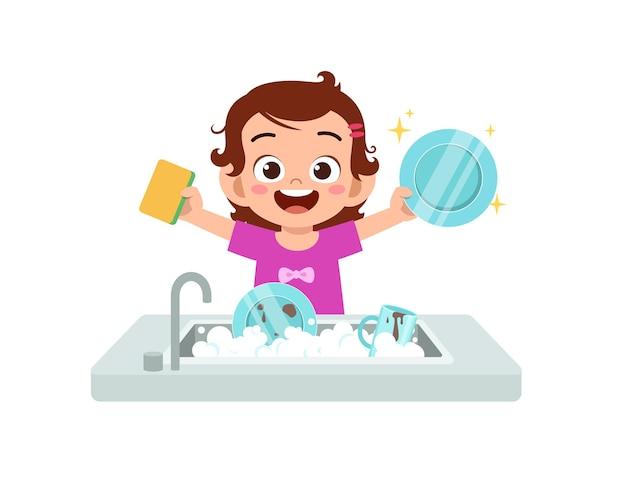 Szczęśliwa śliczna mała dziewczynka do mycia naczyń w kuchni