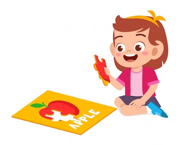 Szczęśliwa śliczna mała dziewczynka gra puzzle