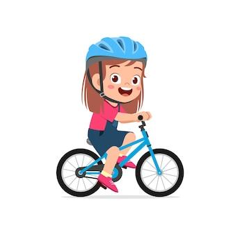 Szczęśliwa śliczna mała dziewczynka jedzie na rowerze