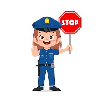 Szczęśliwa śliczna mała dziewczynka nosi mundur policyjny i trzyma znak stop