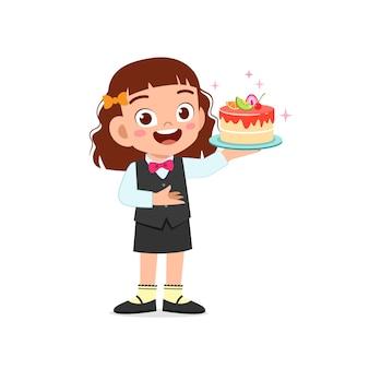 Szczęśliwa śliczna mała dziewczynka ubrana w mundur kelnera i trzymając tort urodzinowy