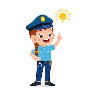 Szczęśliwa śliczna mała dziewczynka ubrana w mundur policyjny i myśli znakiem żarówki
