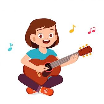 Szczęśliwa śliczna mała nastoletnia dziewczyna bawić się gitarę