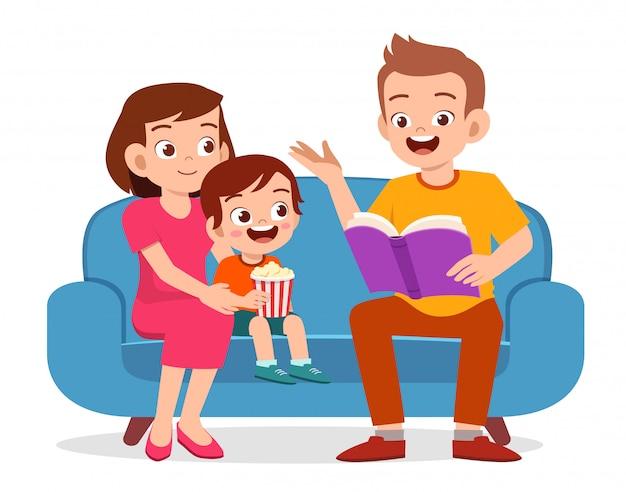 Szczęśliwa śliczna małe dziecko chłopiec czyta książkę z rodzicem