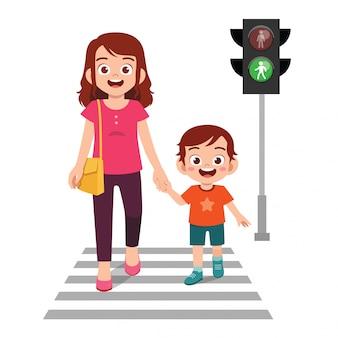 Szczęśliwa śliczna małe dziecko chłopiec krzyżuje drogę z matką