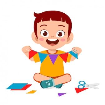 Szczęśliwa śliczna małe dziecko chłopiec robi papierowemu rzemiosłu