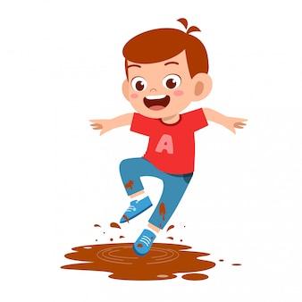 Szczęśliwa śliczna małe dziecko chłopiec skacze na błocie
