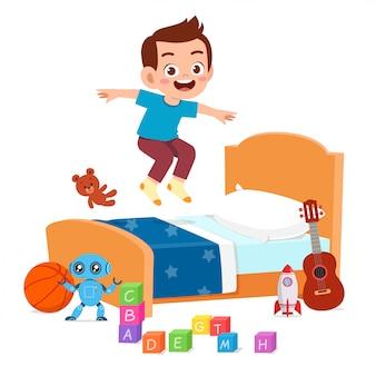 Szczęśliwa śliczna małe dziecko chłopiec skacze na łóżku