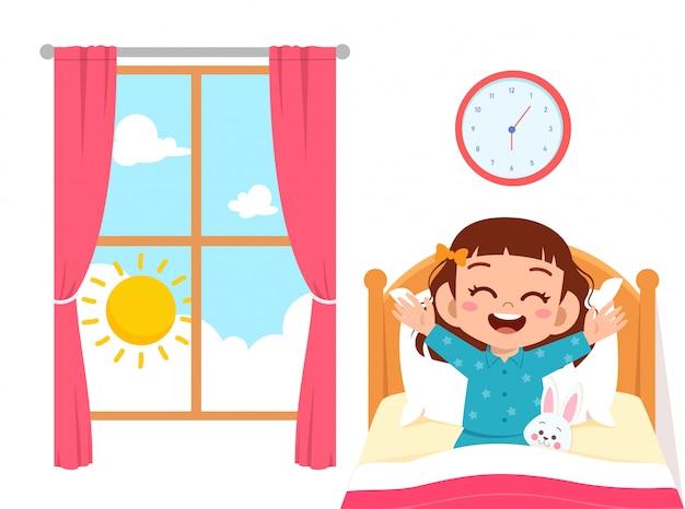 Szczęśliwa śliczna małe dziecko dziewczyna budzi się